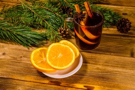 Cup of mulled wine with cinnamon, sliced orange and fir tree branches on rustic wooden table 写真素材