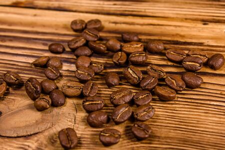 Scattered coffee beans on rustic wooden table 写真素材