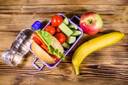Ripe apple, banana, bottle of water and lunch box with hamburger, cucumbers and tomatoes on rustic wooden table. Top view 写真素材