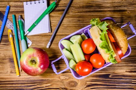 Ripe apple, different stationeries and lunch box with hamburger, cucumbers and tomatoes on rustic wooden table. Top view