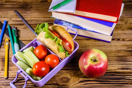 Notepad, pens, ripe apple, stack of books and lunch box with hamburger, cucumbers and tomatoes on rustic wooden table 写真素材