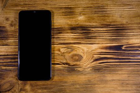 Modern smartphone with blank screen on wooden background. Top view 写真素材