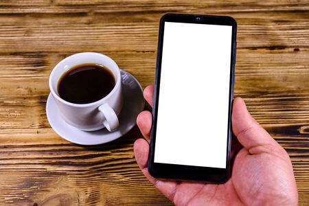 Cup of coffee on wooden background and hand with modern smartphone 写真素材