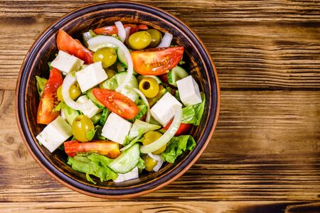 Ceramic plate with greek salad on rustic wooden table. Top view 写真素材