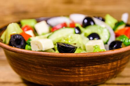 Ceramic plate with greek salad on rustic wooden table 写真素材