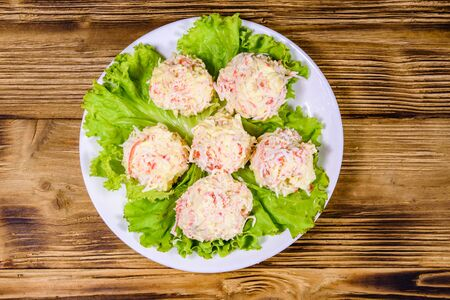 White plate with crab-cheese balls and lettuce leaves on rustic wooden table. Top view