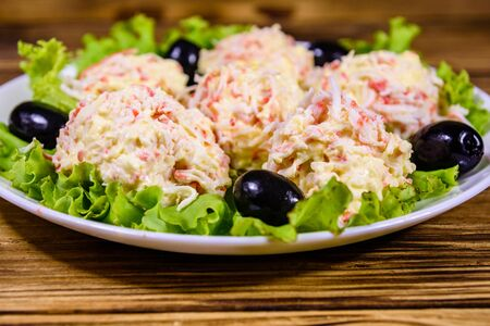White plate with crab-cheese balls, black olives and lettuce leaves on rustic wooden table 写真素材