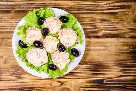 White plate with crab-cheese balls, black olives and lettuce leaves on rustic wooden table. Top view