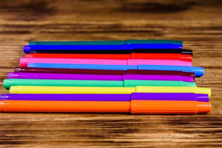 Multi colored felt tip pens on rustic wooden table