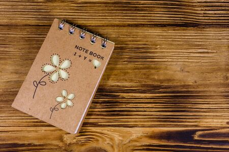 Closed small notepad on rustic wooden table. Top view 写真素材