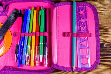 Different school stationeries (pens, pencils, ruler and protractor) in pink pencil box. Top view 写真素材