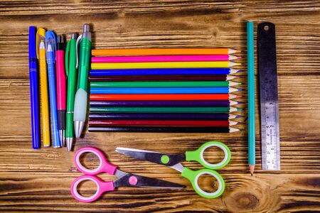 Different school stationeries (pens, pencils, scissors and ruler) on wooden background. Top view