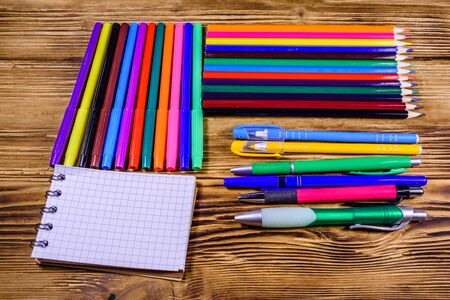 Different school stationeries (pens, notepad, pencils and felt tip pens) on wooden background 写真素材