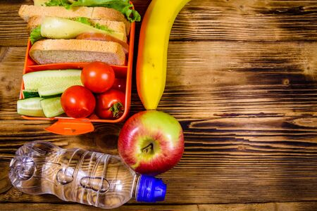Ripe apple, banana, bottle of water and lunch box with sandwiches, cucumbers and tomatoes on rustic wooden table. Top view