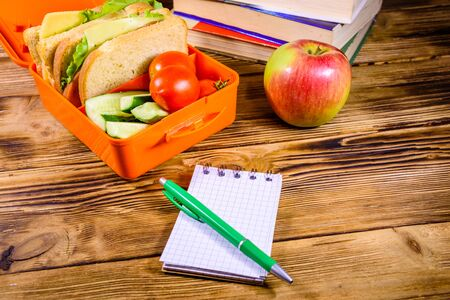 Notepad, pen, ripe apple, stack of books and lunch box with sandwiches, cucumbers and tomatoes on rustic wooden table 写真素材