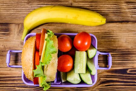 Banana and lunch box with hamburger, cucumbers and tomatoes on rustic wooden table. Top view