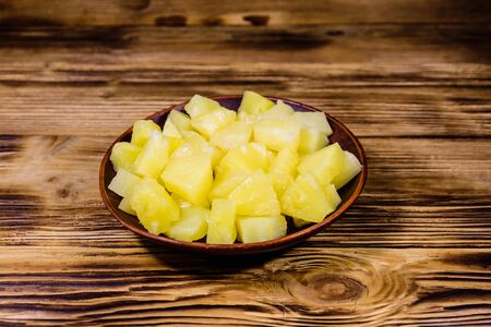 Ceramic plate with chopped canned pineapple on rustic wooden table Stock fotó