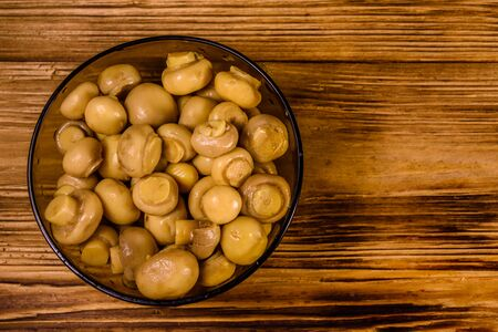 Glass bowl with canned mushrooms on rustic wooden table. Top view Stockfoto