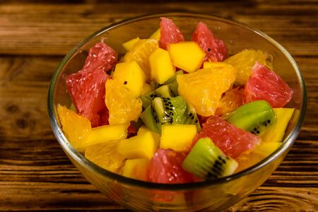 Salad with mango, oranges, grapefruit and kiwi fruits in glass bowl on wooden table Banco de Imagens