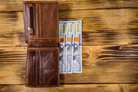 Brown leather wallet and one hundred dollar banknotes on wooden background. Top view Stockfoto