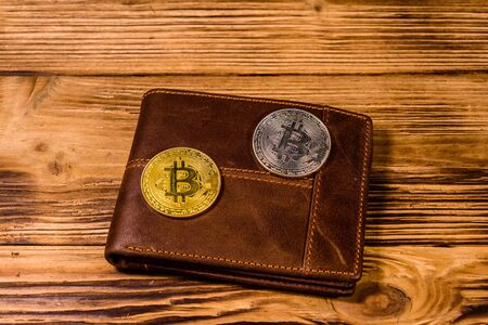 Brown leather wallet and bitcoins on wooden background Stockfoto