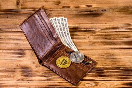 Brown leather wallet, bitcoins and one hundred dollar banknotes on wooden background Stockfoto
