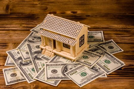 Plywood model of house and one hundred dollar banknotes. Loan, real estate concept Stok Fotoğraf - 129802479