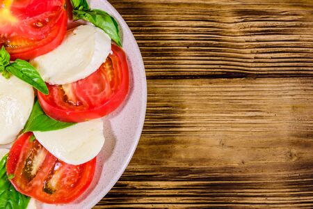 Plate with caprese salad (italian salad with cherry tomatoes, mozzarella cheese and basil leaves) on rustic wooden table. Top view