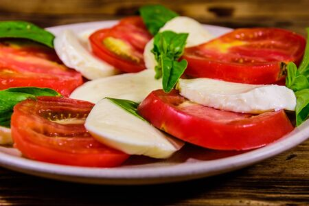 Plate with caprese salad (italian salad with cherry tomatoes, mozzarella cheese and basil leaves) on rustic wooden table