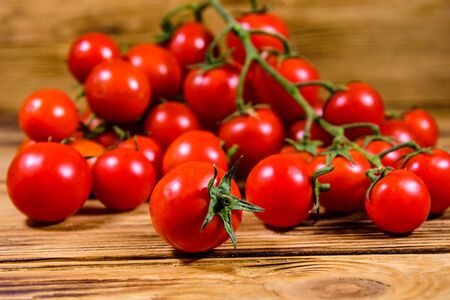 Heap of small cherry tomatoes on rustic wooden table Banco de Imagens