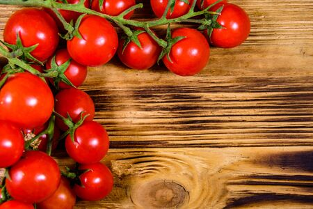 Heap of small cherry tomatoes on rustic wooden table. Top view Banco de Imagens