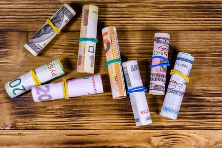 Many rolled up banknotes. Euro, american dollars, ukrainian hryvnias, egyptian pounds and russian roubles Imagens