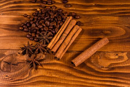 Pile of the coffee beans, star anise and cinnamon sticks on rustic wooden table Stockfoto