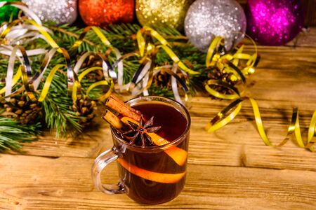 Cup of mulled wine with cinnamon, christmas decorations and fir tree branches on rustic wooden table