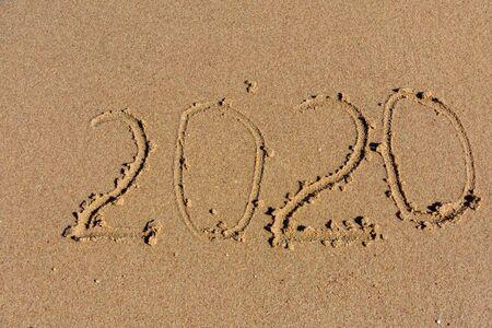 New year 2020. Inscription on sandy beach. Tropical celebration concept Banco de Imagens