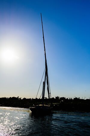 Traditional egyptian vessel felucca moored near bank of Nile river in Luxor, Egypt
