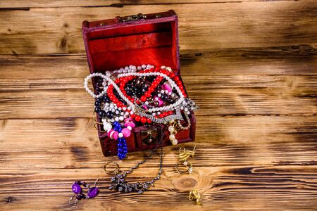 Old box of red wood full of jewelry. Treasure chest