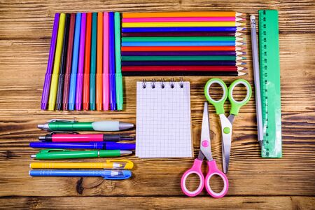 Different school stationeries (pens, notepad, pencils, felt tip pens, scissors and ruler) on wooden background. Top view
