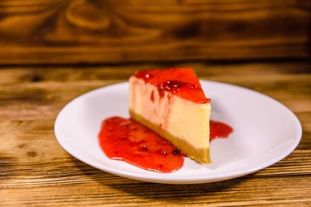 White plate with cheesecake New York and raspberry jam on rustic wooden table Reklamní fotografie