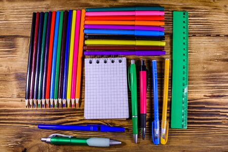 Different school stationeries (pens, notepad, pencils, felt tip pens and ruler) on wooden background. Top view