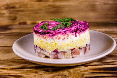 Ceramic plate with russian traditional new year salad herring under fur coat (shuba) and on rustic wooden table Фото со стока
