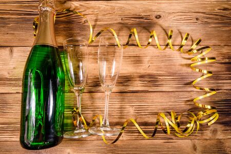 Bottle of champagne and two wineglasses decorated with golden ribbon on rustic wooden table. Top view Stok Fotoğraf