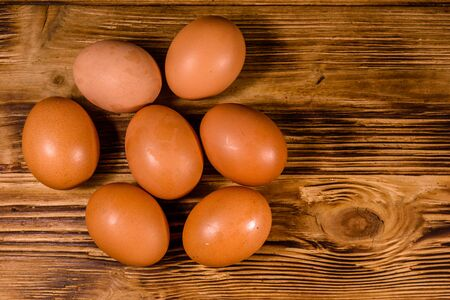 Pile of the hen eggs on rustic wooden table. Top view