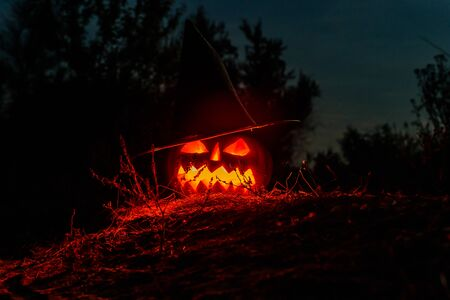 Carved halloween pumpkin jack-o-lantern wearing witch hat with burning candles glows in darkness. Spooky landscape