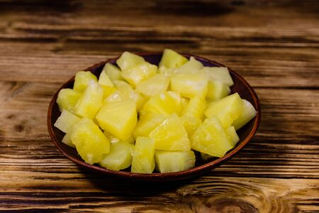 Ceramic plate with chopped canned pineapple on rustic wooden table Stok Fotoğraf
