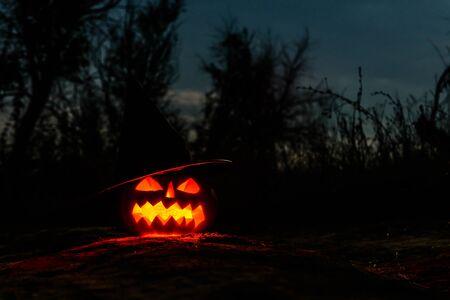 Calabaza de Halloween tallada Jack-o-lantern con sombrero de bruja con velas encendidas brilla en la oscuridad. Paisaje espeluznante