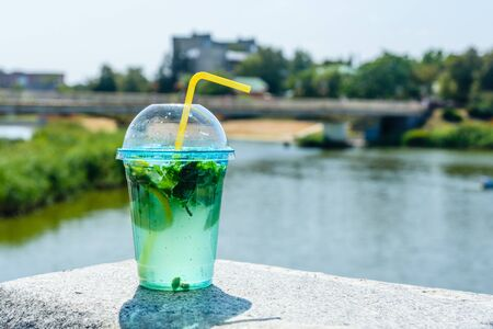 Mojito cocktail on granite parapet with river on background