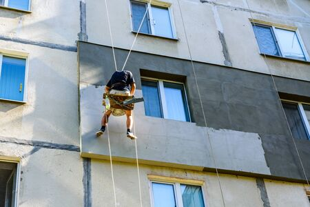 Insulation of apartments in residential building. Rope access working