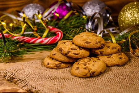 Pile of chocolate chip cookies on sackcloth in front of christmas decorations