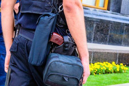 Primer plano de una pistola en la funda en el cinturón de policía